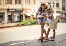 Learning from her mother. Mother teaching her daughter to driving trotline on city street. Copy space royalty free stock images