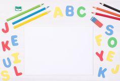 Learning how to read and write. Kid`s desk with blank notebook and colorful letters Stock Images