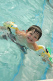Learning how to swim. Little boy wears floaties as he learns to swim Royalty Free Stock Photos