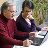 Learning how to use laptop. A brunette woman tutoring a senior man how to use a laptop. They have two laptops on the table in front of them Stock Images
