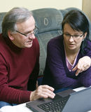 Learning how to use laptop. A woman (daughter) teaching a senior man (father) how to use a laptop Royalty Free Stock Photography