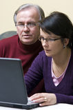 Learning how to use laptop. A woman and senior man looking attentively at a laptop computer screen. They seem very focused on the content Royalty Free Stock Photography