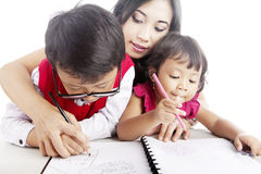 Learning how to write. Young asian mother guiding her children to learn how to write Stock Photography
