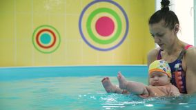Learning infant child to swim in a swimming pool. Swimming instructor learning infant child to swim in a pool. They doing water exercises to hardening and stock video footage