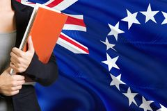 Learning language concept. Young woman standing with the Cook Islands flag in the background. Teacher holding books, orange blank stock image