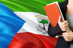 Learning language concept. Young woman standing with the Equatorial Guinea flag in the background. Teacher holding books, orange. Blank book cover stock photos