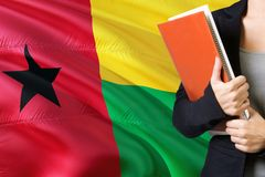 Learning language concept. Young woman standing with the Guinea Bissau flag in the background. Teacher holding books, orange blank. Book cover stock images