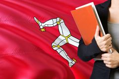 Learning language concept. Young woman standing with the Isle Of Man flag in the background. Teacher holding books, orange blank royalty free stock photography