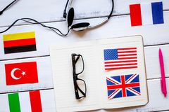 Learning language lifestyle in online school concept on table to. Learning foreign language lifestyle in online school concept with copybook, earphones and flags Royalty Free Stock Images