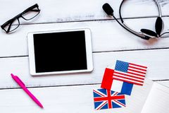 Learning language lifestyle in online school concept on table to. Learning foreign language lifestyle in online school concept with copybook, flags and tablet on Royalty Free Stock Photography