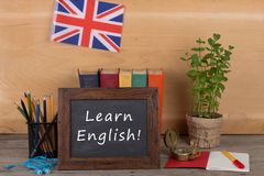 blackboard with text & x22;Learn English!& x22;, flag of the United Kingdom, books, pencils, compass Stock Photography