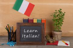 "Learning languages concept - blackboard with text ""Learn italian!"", flag of the Italy, books, chancellery. On table and wooden background stock photo"