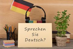 Paper with text & x22;sprechen sie deutsch?& x22;, flag of the Germany, books, headphones, pencils. Learning languages concept - paper with text & x22;sprechen Stock Photo