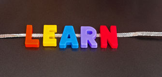 Learning on line. Text ' learning on line ' with colorful uppercase letters  on a silver ribbon providing a concept of  learning over the internet Stock Photography