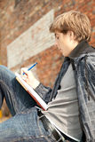 Learning male student. Sitting male student learning near the brick wall Royalty Free Stock Photography