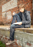 Learning male student. Sitting male student learning near the brick wall Royalty Free Stock Photo