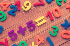 Learning math calculation. Five add five, simple math addition on wooden background. Cross processed to create retro effect Stock Photography