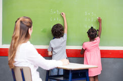 Learning mathematics at elementary school. Multi ethnic students. Writing on chalkboard with teacher observing Royalty Free Stock Photos