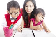 Learning with mom. Portrait of young asian mother guiding her children to draw and write on the paper Stock Image