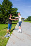 Learning mother and daughter on roller skates Royalty Free Stock Image