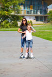 Learning mother and daughter on roller skates Royalty Free Stock Photos