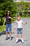 Learning mother and daughter on roller skates Stock Photo