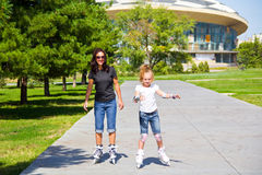 Learning mother and daughter on roller skates Royalty Free Stock Photography