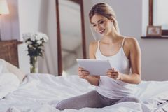 Pretty young woman watching video tutorial on bed stock photos