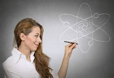 Learning physics science. Portrait attractive woman, teacher explaining physics lessons in class, standing by blackboard. Education, research, knowledge royalty free stock image