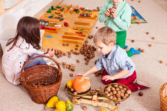 Learning through play. Children in kindergarten playing and exploring the concept of balance using weights Stock Image