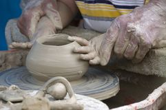 Learning pottery. Potter's hands helping young student in pottery Stock Image