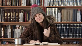Face portrait girl in winter clothes in bookstore stock video footage