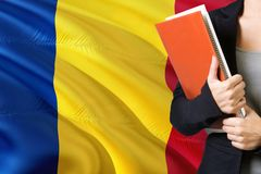 Learning Romanian language concept. Young woman standing with the Romania flag in the background. Teacher holding books, orange stock photo