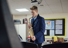 Learning Saxaphone At School. Male student is practicing saxaphone after school in the music room Royalty Free Stock Image