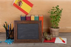 Learning Spanish language concept - blank blackboard, flag of the Spain, books, pencils, compass. On wooden background Stock Image