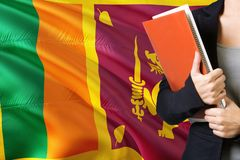 Learning Sri Lankan language concept. Young woman standing with the Sri Lanka flag in the background. Teacher holding books, stock photos