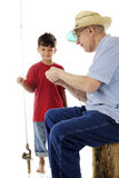Learning to Bait the Hook. An adorable preschooler happily watching his grandpa bait a fishing hook.  On a white background Stock Image
