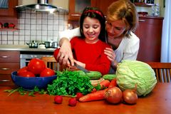 Learning to cook. Sweet little seven year old girl is learning from her mom how to make a delicious salad, in the home kitchen Stock Images