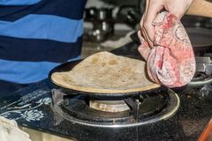 Learning to cook Parantha in India royalty free stock image