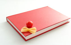 Learning to cook together. Red cook-book with tomato and pasta on white background Royalty Free Stock Photography