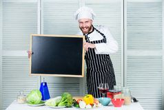 Learning to cook vegetables. Man holding empty blackboard. Chief cook teaching master class in cooking school. Master royalty free stock photos