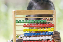 Learning to count in school - African school girl portrait. African girl counting on abacus education symbol Stock Photography