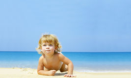 Learning to crawl. Portrait of blond blue eyed baby crawling through the beach Royalty Free Stock Photography