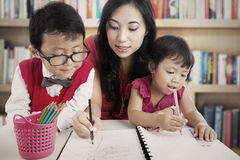 Learning to draw in library. Portrait of young asian mother guiding her children to draw and write on the paper. shot in the library Royalty Free Stock Image