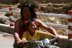 Learning to drive. Tibetan man teaching his daughter to ride a motorcycle, Tibet Stock Photography