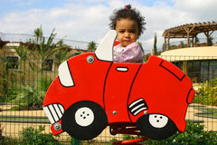 Learning to Drive. A young mixed race girl in a toy car Stock Photo