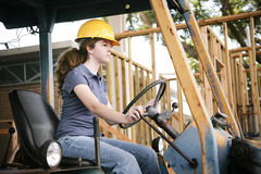 Learning to Drive Bulldozer. Young female construction apprentice learning to drive heavy equipment Stock Photo