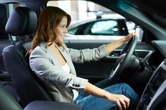 Learning to drive. Cheerful young woman learning to drive on her own Royalty Free Stock Images
