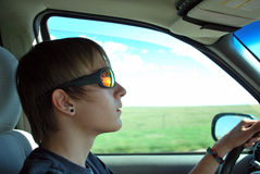 Learning To Drive. Teenage boy learning to drive in the country.He has a reflection of clouds in his glasses Stock Images