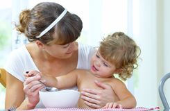 Learning to eat. Portrait of young woman feeding her baby daughter Royalty Free Stock Image